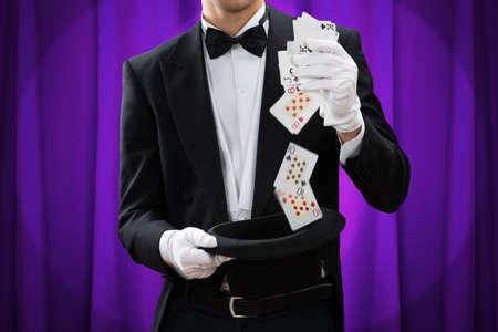 mago: Sección media de truco Ejecución del mago de sexo masculino con las tarjetas y el sombrero contra la cortina púrpura Foto de archivo