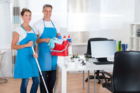 cleaner: Two Happy Cleaners With Cleaning Equipments In Office