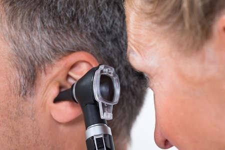 pacientes: Primer Plano De Una Doctora Examen del o�do del paciente con otoscopio