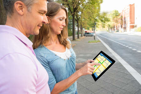 touch screen: Happy Couple Looking At Gps Map On Digital Tablet