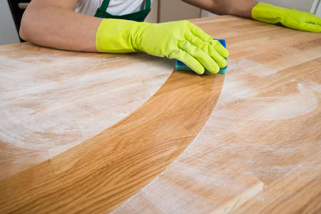 Cropped image of man cleaning dust on wooden table at home