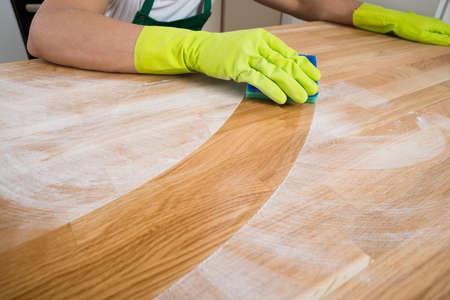 Imagen recortada de polvo de limpieza hombre en la mesa de madera en el hogar Foto de archivo