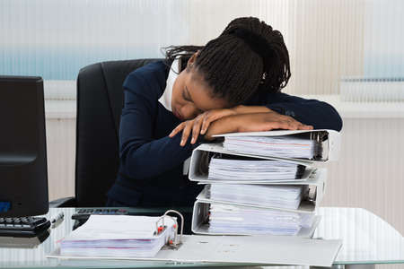 stressed business woman: Young African Businesswoman Sleeping On Stacked Of Files