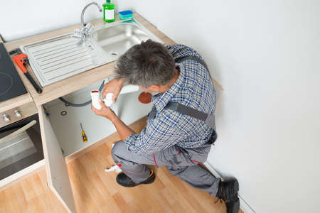 plumber: Side view of mature plumber fixing sink pipe in kitchen