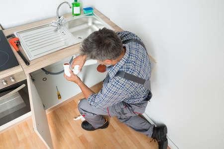 fontanero: Vista lateral de fontanero madura la fijación de la tubería del fregadero en la cocina