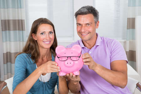 financial planning married: Portrait Of A Smiling Couple Holding Piggybank