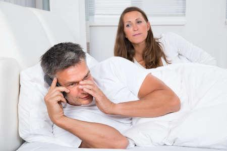 Esposas: Mirando a la mujer Hombre hablando por teléfono móvil en el dormitorio Foto de archivo