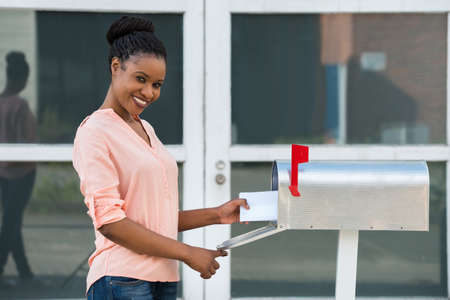 incoming: Smiling Young African Woman Collecting Her Mail From Mailbox