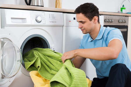 dirty room: Young man loading towels in washing machine at home