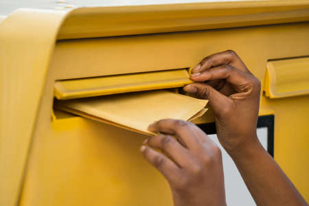 retrieve: Close-up Of A Persons Hand Inserting Letter In Mailbox
