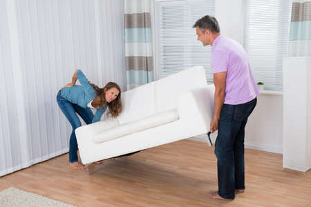 carry on: Man Looking At Woman Suffering From Backache While Moving Sofa Stock Photo