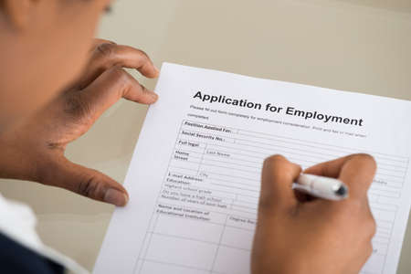 unemployment: Close-up Of A Woman Filling Employment Form Stock Photo