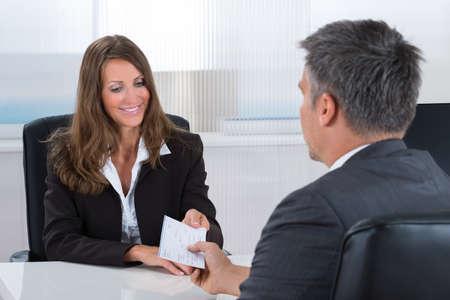 chequera: Empresaria feliz que da Cheque Para empresario en la oficina