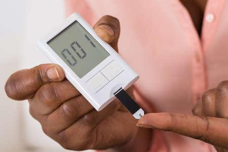 diabetes: Primer plano de la mano de retención de dispositivo para la medición de azúcar en la sangre