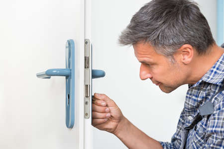 lock: Male carpenter fixing lock in door with screwdriver at home