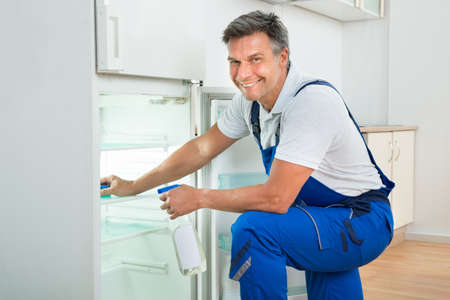 cleaning service: Side view of mature janitor cleaning refrigerator with spray bottle and sponge at home