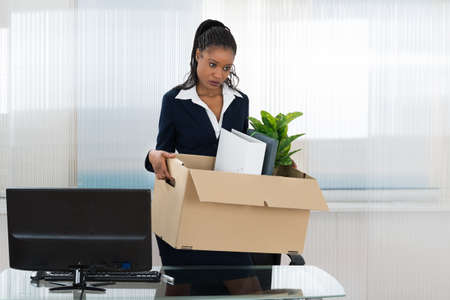 transferred: Sad African Businesswoman Carrying Box With Her Belongings In Office