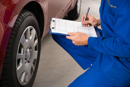 the clipboard: Escribir Mecánico joven en el sujetapapeles blanco el examen de la rueda de coche Foto de archivo