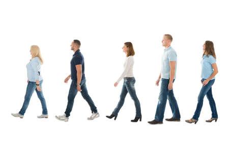 in row: Integral vista lateral de hombres y mujeres que caminan en la cola aislado en el fondo blanco