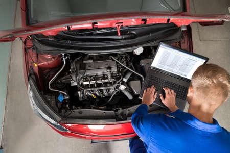 garage automobile: Vue en plongée de Mechanic examen moteurs de voitures avec l'aide d'un ordinateur portable