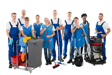 Portrait of happy janitors with cleaning equipment standing against white background Foto de archivo