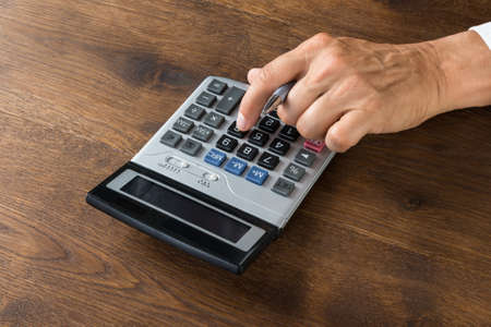 account executives: Cropped image of businessman using calculator at wooden desk