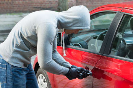 lawbreaker: Thief In Hooded Jacket Using Tool And Trying To Steal Car Stock Photo
