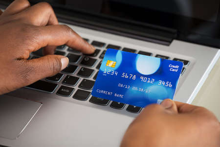 woman holding card: Close-up Of A Persons Hand Using Debit Card While Shopping Online On Laptop Stock Photo