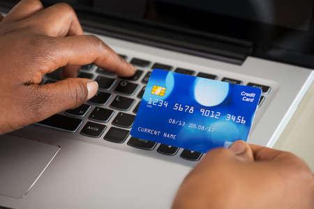 usando computadora: Primer plano de la mano de una persona mediante tarjeta de débito mientras compras en línea en la computadora portátil