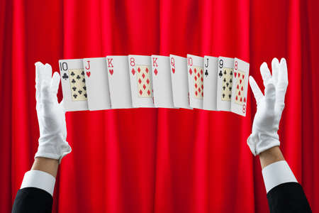 magician: Cropped hands of magician performing trick with cards against red curtain