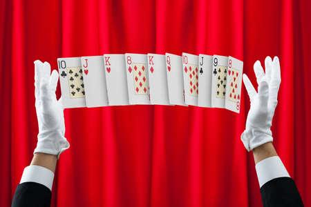 mago: manos recortadas de mago haciendo trucos con cartas contra la cortina roja