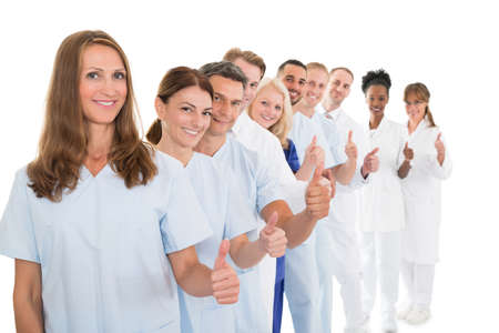 Portrait of confident medical team showing thumbs up while standing in line against white background Standard-Bild