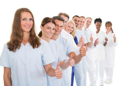 Portret van vertrouwen medisch team zien thumbs up tijdens het staan in de rij tegen een witte achtergrond Stockfoto