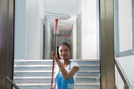 cleaning services: African Woman Cleaning Glass With Rubber Window Cleaner Stock Photo