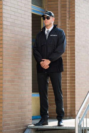 agent de sécurité: Jeune Garde de sécurité Homme debout à l'entrée