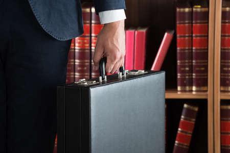 Buik van advocaat met aktetas tegen boekenplank in rechtszaal Stockfoto