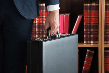 Midsection of lawyer carrying briefcase against bookshelf in courtroom