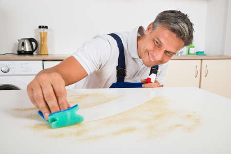 sponge: Smiling male janitor cleaning counter with sponge at home Stock Photo