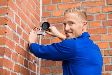 setup man: Close-up Of Smiling Technician Installing Camera On Brick Wall