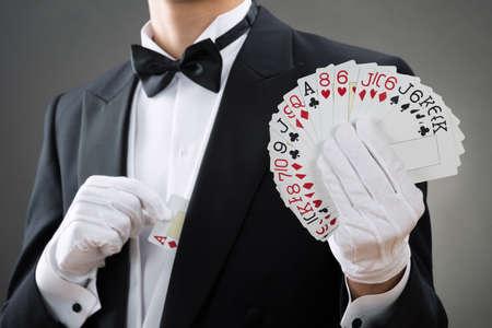 Buik van goochelaar het tonen waaierde uit kaarten tegen de grijze achtergrond