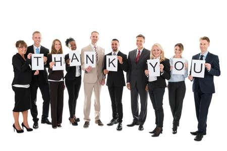 Full length portrait of smiling business team holding Thank You sign against white background Standard-Bild