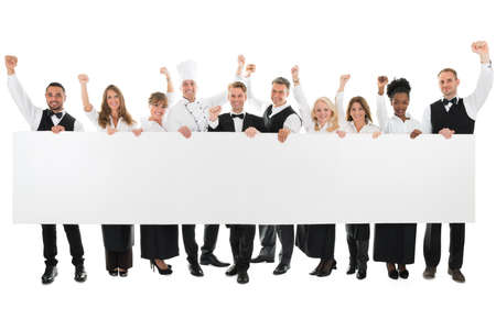 woman holding sign: Portrait of happy restaurant staff with arms raised holding blank billboard against white background Stock Photo