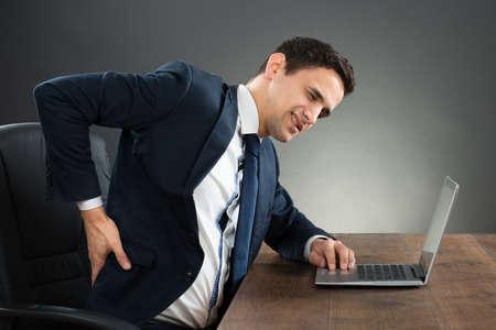 espalda: Hombre de negocios joven que sufre de dolor de espalda mientras se trabaja en la computadora portátil en el escritorio contra el fondo gris Foto de archivo