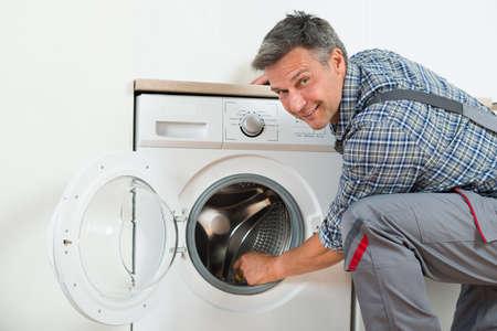 technician: Side view of repairman checking washing machine at home