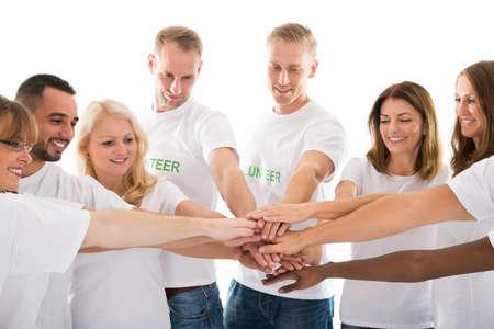 obra social: Voluntarios multiétnico feliz de apilamiento manos mientras está de pie contra el fondo blanco