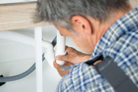 fontaneria: Recorta la imagen de militar que trabaja en las tuberías debajo del fregadero de la cocina