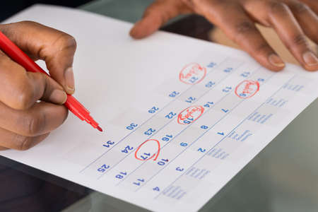 event organizer: Person Circling Important Date On Calendar With Red Marking