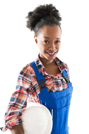 Portrait of smiling female carpenter holding hardhat standing against white background