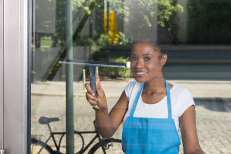 clean window: African Woman Cleaning Glass With Rubber Window Cleaner From Outside