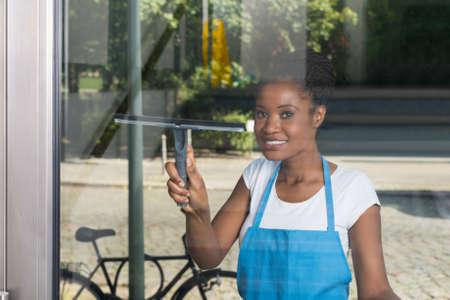 mujer trabajadora: Ventana africana limpieza de la mujer Vidrio Con Rubber Cleaner Desde el exterior